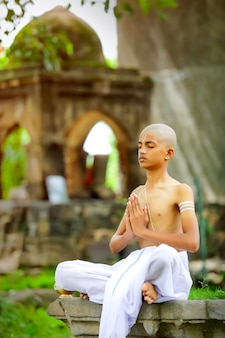Indisches priesterkind, das yoga im park tut