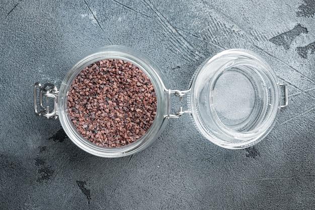 Indisches schwarzes salz, kala namak hindi gesundes nahrungsmittelkonzeptset, im glas, auf grauem stein