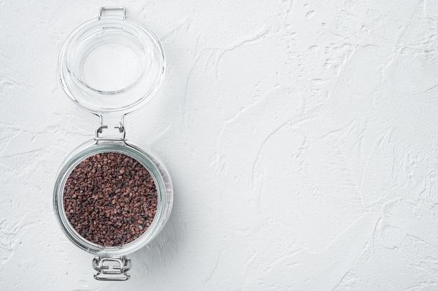 Indisches schwarzes salz, kala namak hindi gesundes nahrungsmittelkonzeptset, im glas, auf weißem stein