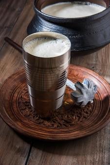 Indisches süßes lassi aus milch, quark, zucker und salz gemischt mit eiswürfeln, serviert in einem jumbo-stahlglas, zubereitet im traditionellen tontopf