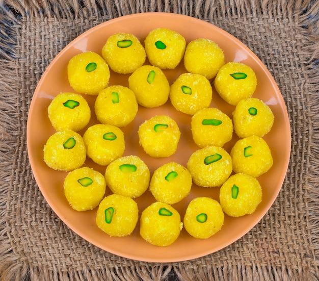 Indisches süßes lebensmittel-kokosnuss laddu auf hölzernem hintergrund