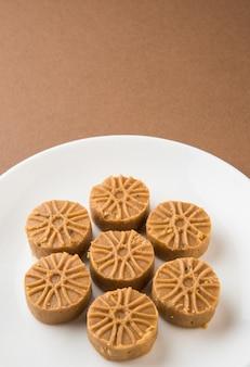 Indisches süßes peha oder pera, festivalessen, serviert auf weißem keramikteller, isoliert auf buntem hintergrund