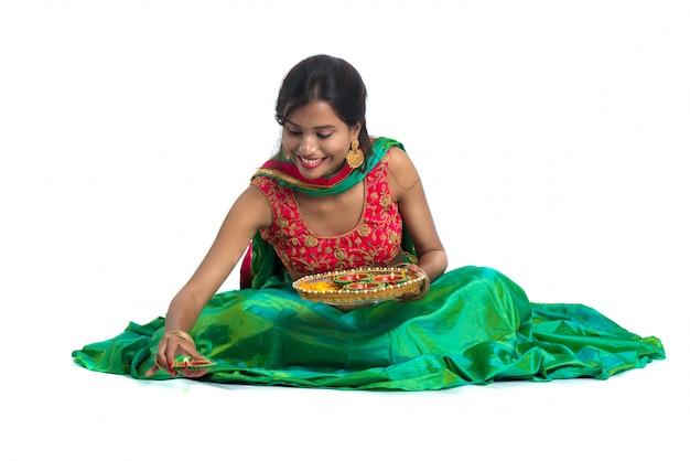 Indisches traditionelles mädchen, das diya hält und diwali oder deepavali feiert