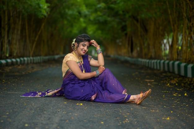 Indisches traditionelles schönes junges mädchen im saree, das draußen aufwirft