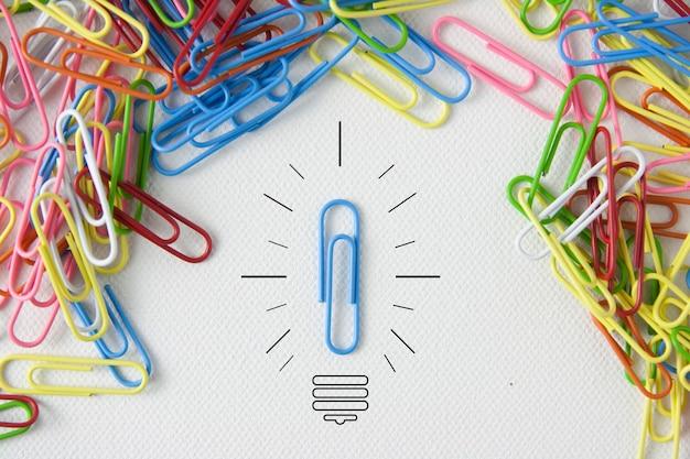 Individualitätssymbol und unabhängiges denkerkonzept und neues führungskonzept oder individualität als gruppe von büroklammern auf leinwand mit einer person in die entgegengesetzte richtung als geschäftsikone.