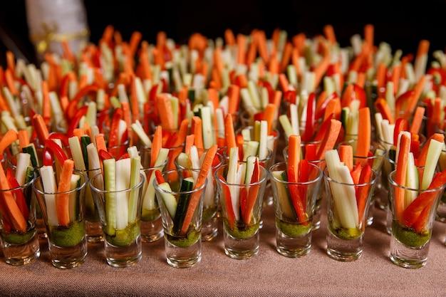 Individuelle cocktail-schnapsgläser mit karotten-, gurken- und pikanter sauce.