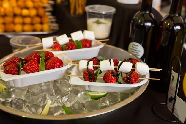 Individuelle dessert-kebabs mit erdbeeren und marshmallows, beträufelt mit schokoladensauce, serviert auf einwegtabletts und bleiben kühl in einer mit eis gefüllten schüssel auf dem buffettisch