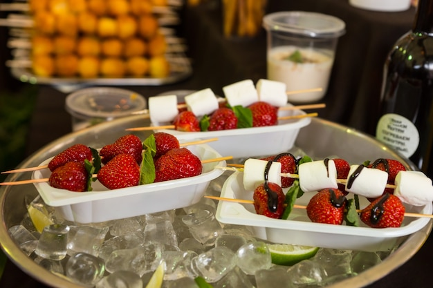 Individuelle dessert-kebabs mit erdbeeren und marshmallows, beträufelt mit schokoladensauce, serviert in tabletts zum mitnehmen und kühl in einer schüssel mit eis auf dem buffettisch