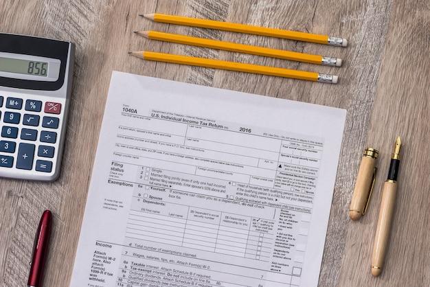 Individuelles steuerformular mit taschenrechner, kugelschreiber und bleistift