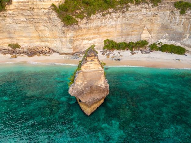 Indonesien. ein schmaler streifen leeren wilden strandes nahe dem felsigen ufer. einsame malerische insel in ufernähe. luftaufnahme
