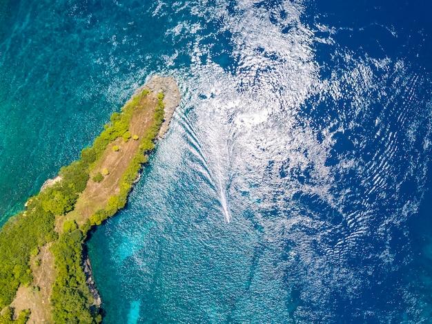 Indonesien. smaragdgrüne oberfläche des ozeans. ein kleiner bootstrimaran in der nähe einer tropischen insel, bewachsen mit dschungel. luftaufnahme senkrecht nach unten