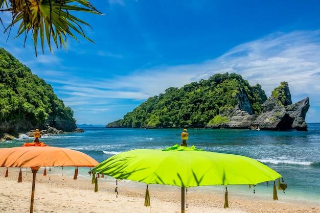 Indonesien. sonnenschirme am strand. smaragdwasser. felsinsel im ozean, bedeckt mit dschungel