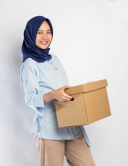 Indonesierin im hijab, der eine kiste hebt