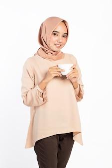 Indonesierin in hijab, die eine tasse tee oder kaffee hält