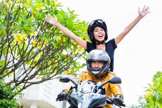 Indonesische frau, die auf motorrad frei sich fühlt