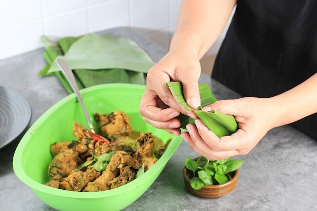 Indonesische frau eingewickelt gelbes curry-huhn mit bananenblatt-kochprozess, der pepes ayam . macht