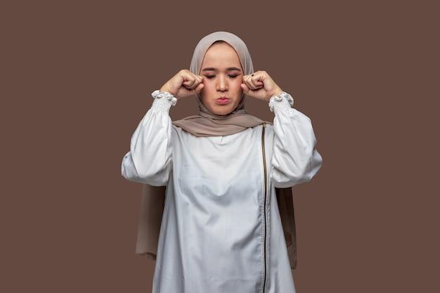 Indonesische frau hijab posiert weinen und traurigen ausdruck isoliert auf einfarbigem hintergrund