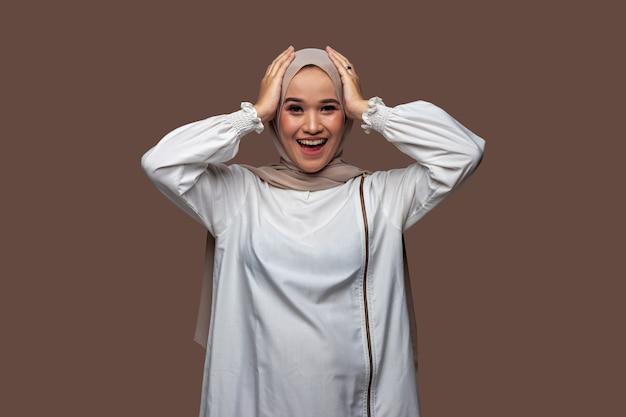 Indonesische frau im hijab hält den kopf beim lächeln