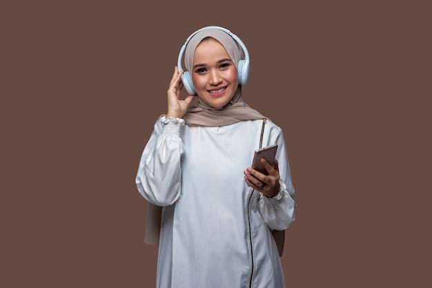 Indonesische frau im hijab posiert mit kopfhörern und hält handy
