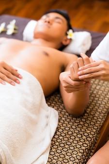 Indonesischer asiatischer mann im wellness-schönheitsbad mit aromatherapie-handmassage mit ätherischem öl, das entspannt aussieht