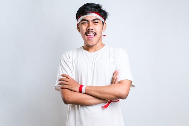 Indonesischer junge doung verschränkte arme mit rotem und weißem stirnband. blick in die kamera. positive person.