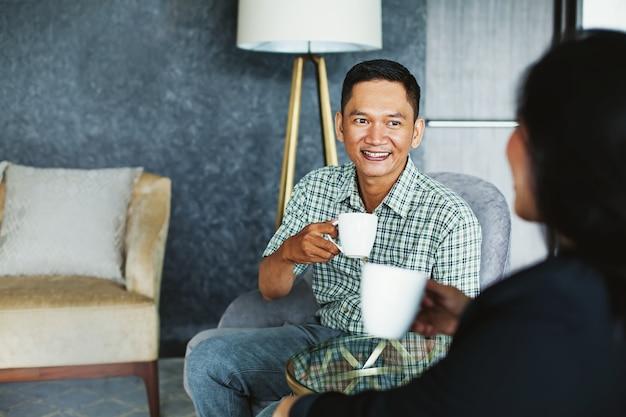 Indonesischer mann trinkt kaffee mit seinem partner