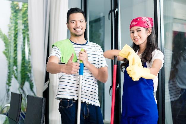 Indonesisches ehepaar putzt sein haus, frau und ehemann helfen sich gegenseitig bei der hausarbeit