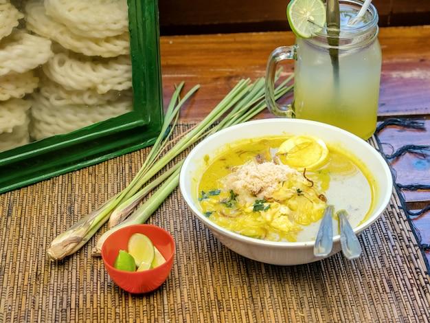 Indonesisches essen soto serviert mit limettenscheiben