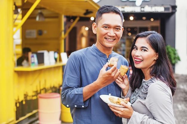 Indonesisches paar, das traditionelles straßenessen isst