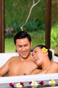Indonesisches paar, das wellnessbad im spa hat