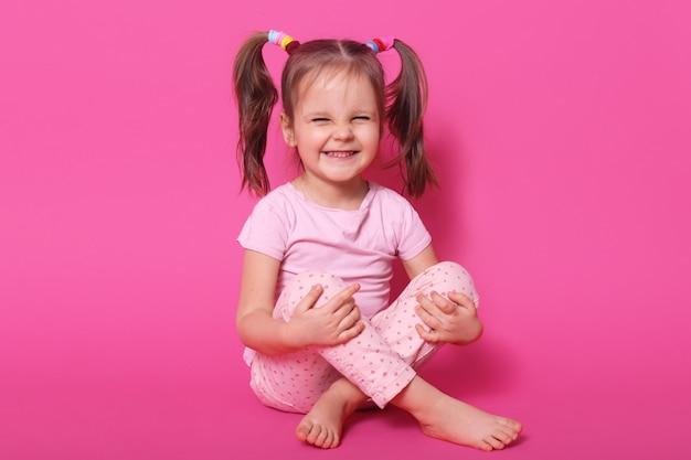 Indoor lachendes positives kind sitzt auf dem boden, posiert isoliert auf rosa, trägt rosent-shirt und -hose, hat pferdeschwänze, ist in hochstimmung. kindheitskonzept.