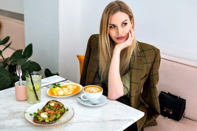 Indoor-porträt des lebensstils der stilvollen jungen blonden geschäftsfrau, die ihren brunch im hipster-café genießt, nach kellner fragend und lächelnd