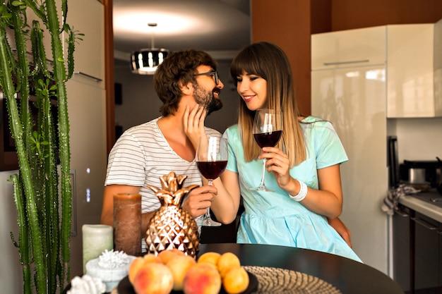 Indoor romantisches familienporträt des hübschen jungen ehepaares, das romantischen abend zusammen verbringt, rotwein zu hause trinkend entspannt.