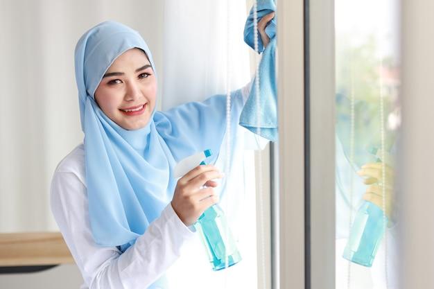 Indoor-schuss aktive junge schöne asiatische muslimische hausfrau frau, die reinigungsspray hält