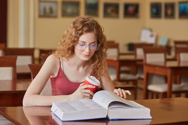 Indoor shopt von studentin, die in der bibliothek ist, buch liest und kaffee trinkt, zeit in der bibliothek verbringt, sich auf klassen vorbereitet, frau, die kastanienbraunes t-shirt trägt, sieht konzentriert aus. bildungskonzept.