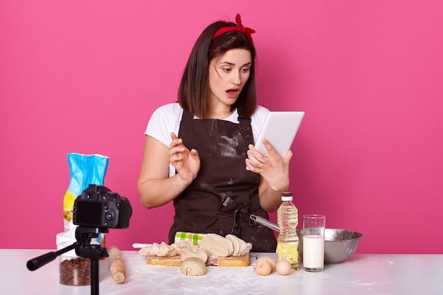 Indoor-studioaufnahme eines konzentrierten bloggers, der das kulinarische tutorial auf dem tablet betrachtet