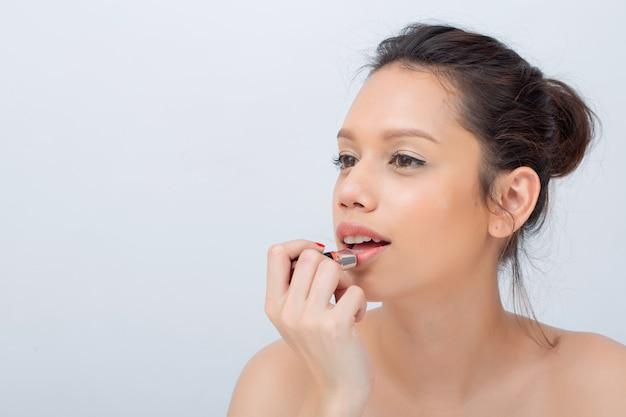 Indoor-studioaufnahme für die schöne asiatische frau, die breit lippenstift mit natur-make-up anwendend lächelt