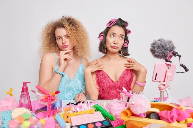 Indoor-vloggerinnen tragen festliche kleidung, umgeben von schönheitsprodukten, bereiten sich auf das date vor. influencer-marketing