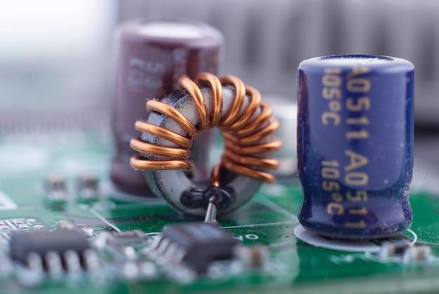 Induktor mit motherboard-hintergrund. chipplatine der computerplatine. hardware-konzept der mikroelektronik.