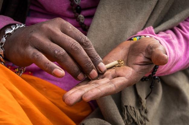 Indus sadhu stellt mit seinen händen eine drogenmischung her. mischt tabak und hanf. guru-lehrer macht ein räuchermischung haschisch
