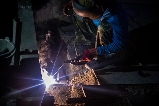 Industrie schweißarbeiter mit einem metallrohr in fabrik mit funkenlicht