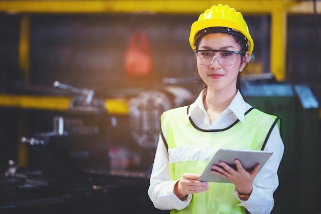 Industrieanlage für frauen mit einer tablette in der hand, ingenieur, der an der einrichtung von industriemaschinen in der fabrik sucht.