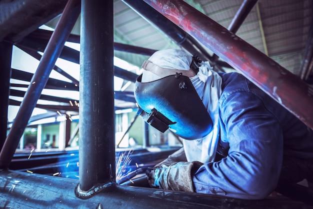 Industriearbeiter am fabrikschweißen, stahlrohrstruktur schweißend