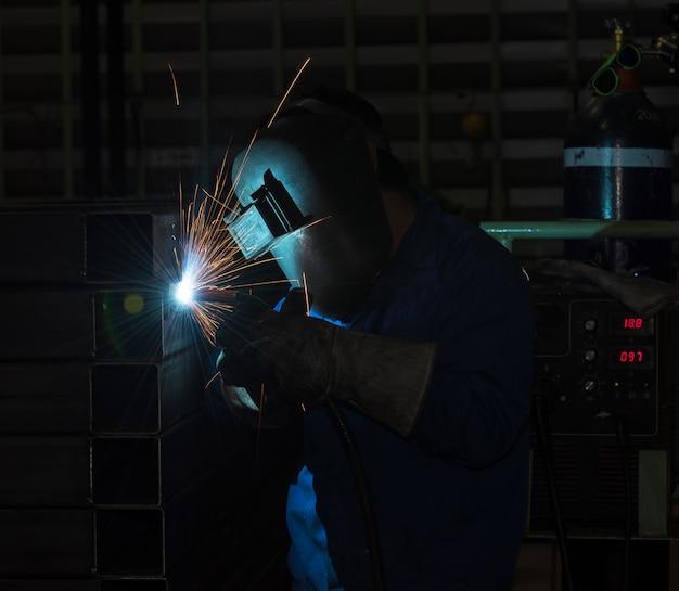 Industriearbeiter am fabrikschweißen, stahlstruktur schweißend