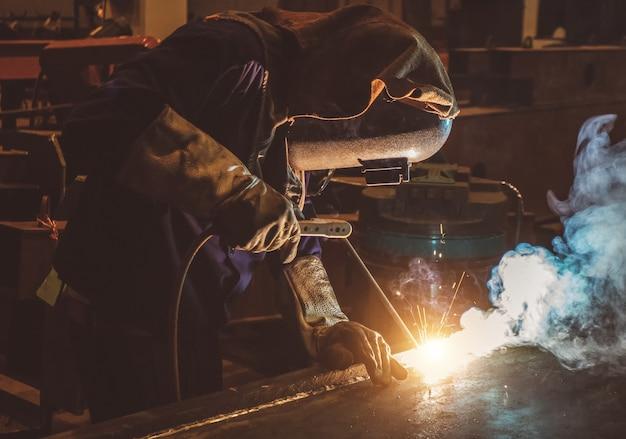 Industriearbeiter arbeiter in der fabrik, die stahlkonstruktion schweißt