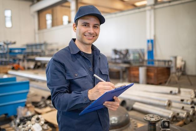 Industriearbeiter, der auf ein dokument in einer fabrik schreibt