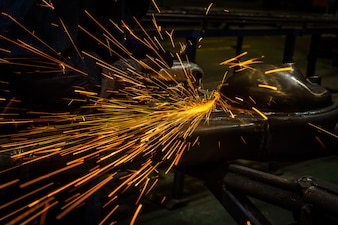 Industriearbeiter, der Metall mit Schleifer schneidet