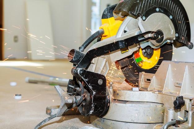 Industriearbeiter, der metall mit vielen scharfen funken schneidet und schweißt