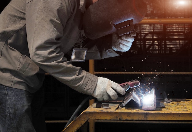 Industriearbeiter, die auf einer industrieanlage schweißen.