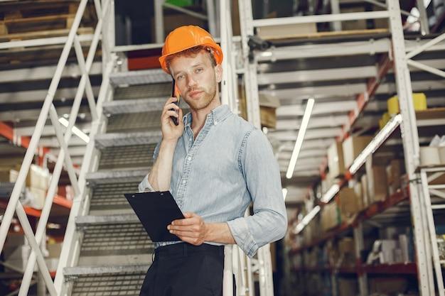 Industriearbeiter drinnen in der fabrik. geschäftsmann mit orangefarbenem schutzhelm. mann in einem blauen hemd.